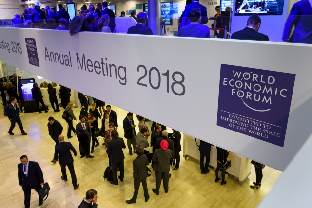 Merkel, Macron take Davos spotlight ahead of Trump show