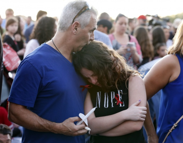 Tears and guilt grip survivors at US school shooting vigils